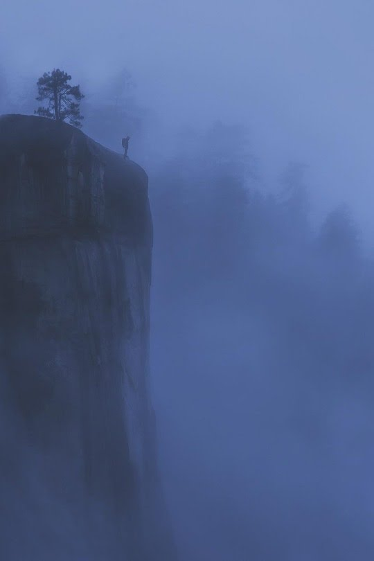 man standing of cliff in fog