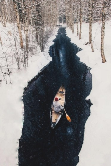 man paddling down creek surrounded by snow