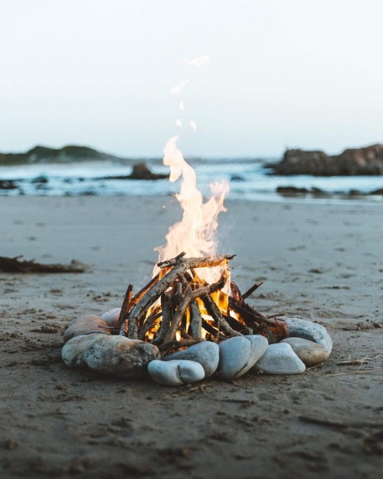 campfire surrounded by rocks on beach