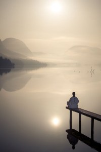 man meditating on lake dock