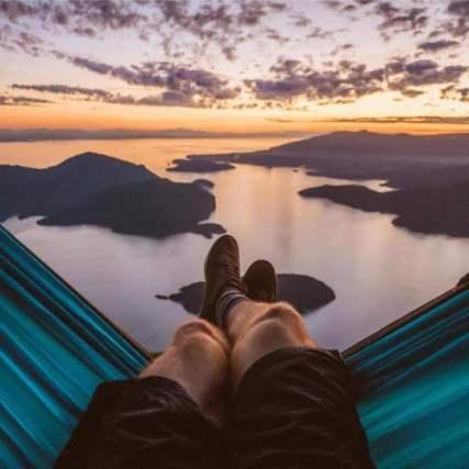 man relaxing in hammock looking at beautiful sunset