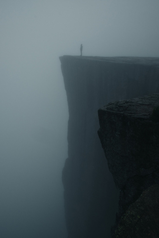 man standing on foggy cliff