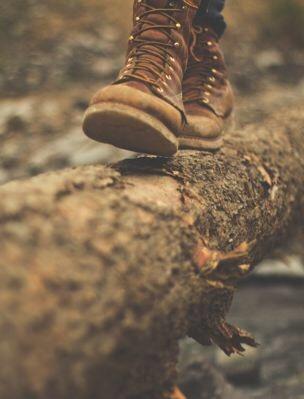 man wearing boots walking on log