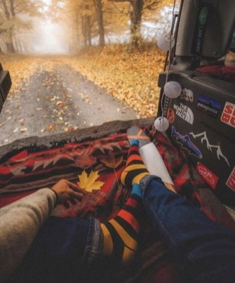 man with colorful socks looking out back of van on a fall day