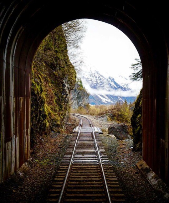 railroad track and tunnel with mountain