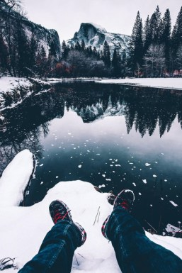 relaxing in the snow at the edge of a mountain lake