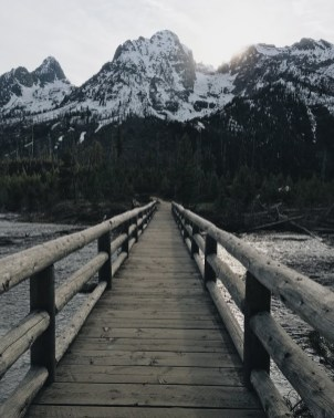 wooden walkway that leads to mountains
