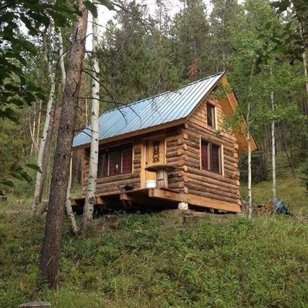little log cabin on a hill