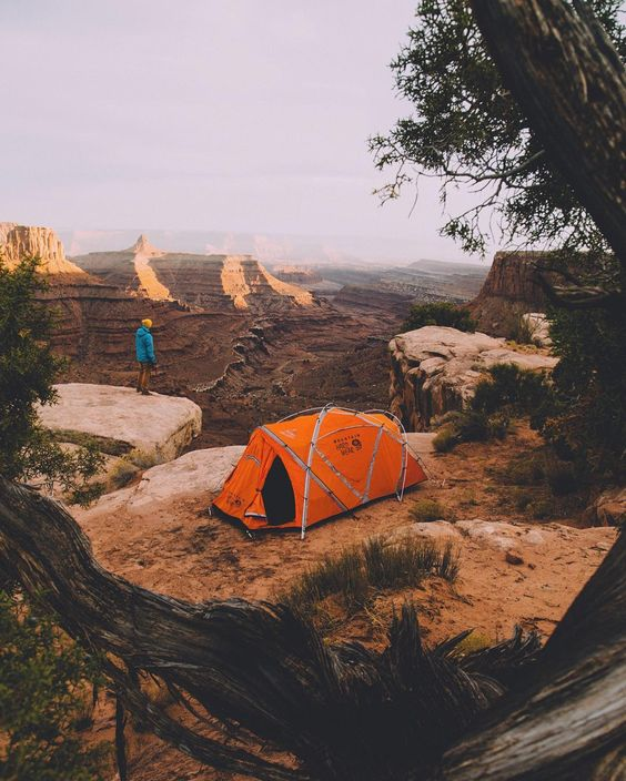 man standing near tent on edge of canyon
