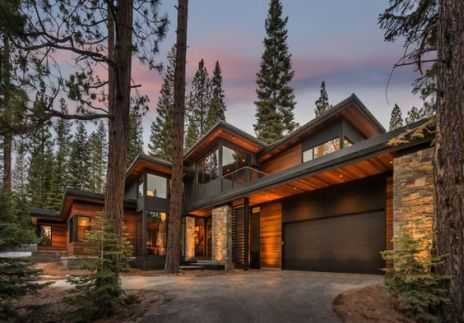 wood and stone trim home in the woods