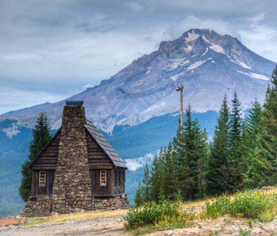 stone fireplace on wood cabin with mountain in background