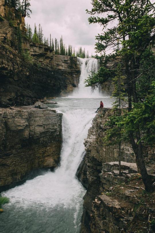 woman sitting near edge of waterfall