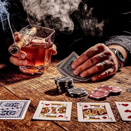 man playing poker drinking whickey and smoking a cigar
