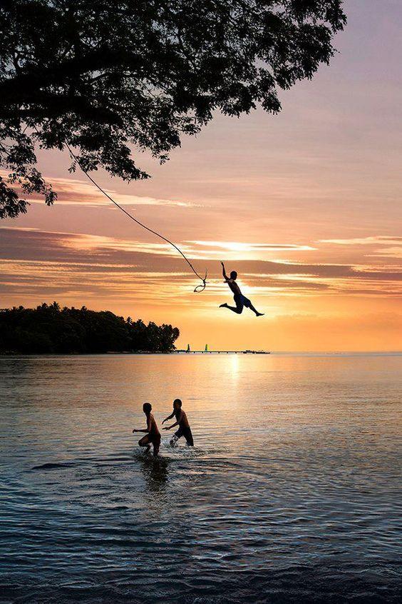 kids playing on rope swing at lake