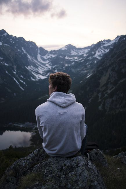 man sitting on ledge looking at mountains