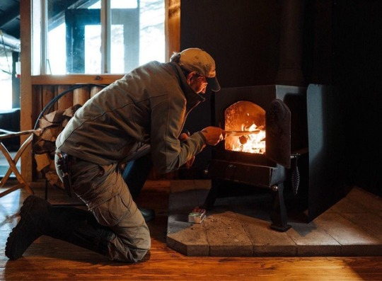 man tending to fire in wood burning stove
