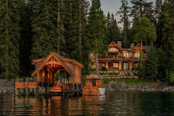 large rustic lake home with covered dock and boat