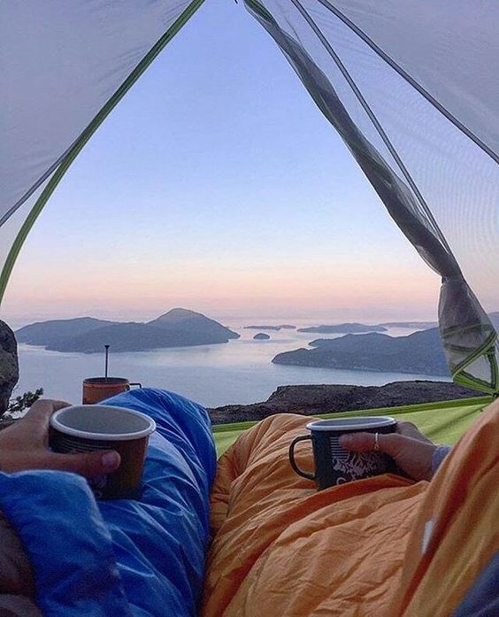 man and woman looking out of tent admiring view