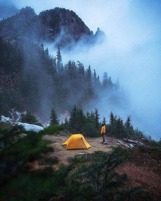 man standing near mountain campsite