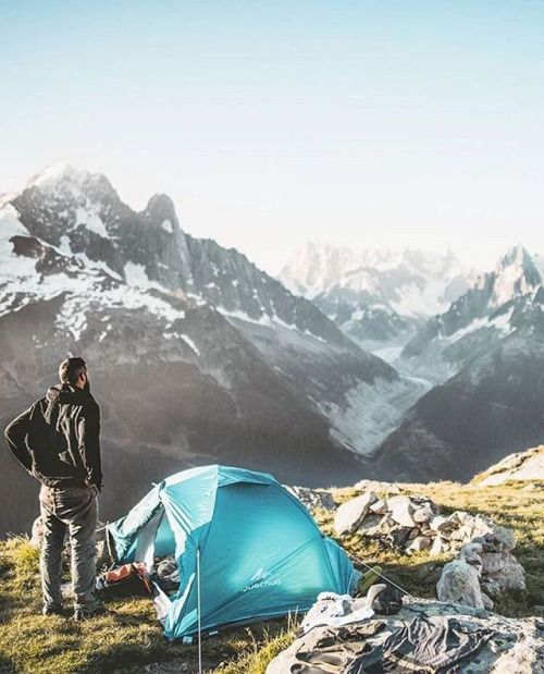 man standing near tent admiring mountain view
