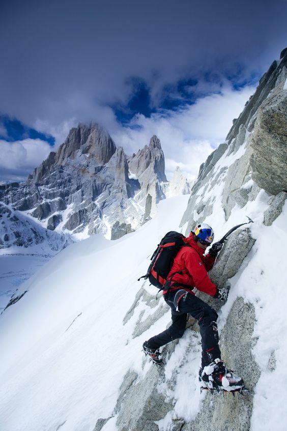 man climbing a snow-covered mountain
