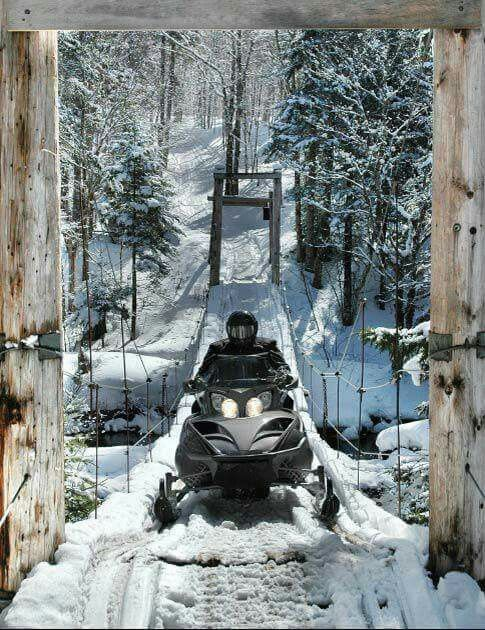 man on a snowmobile crossing bridge