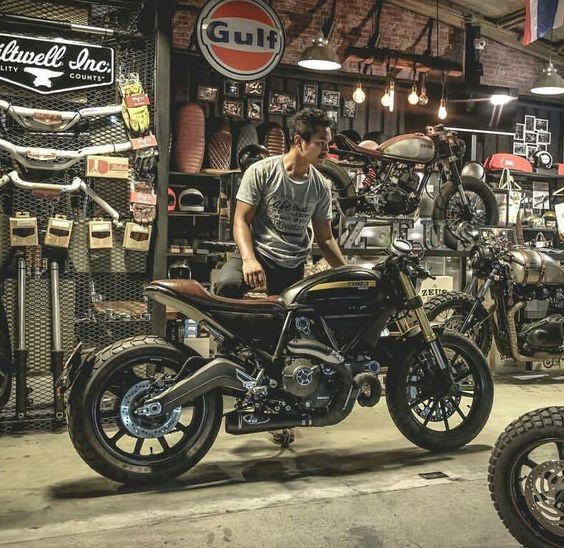man standing next to bike in motorcycle shop