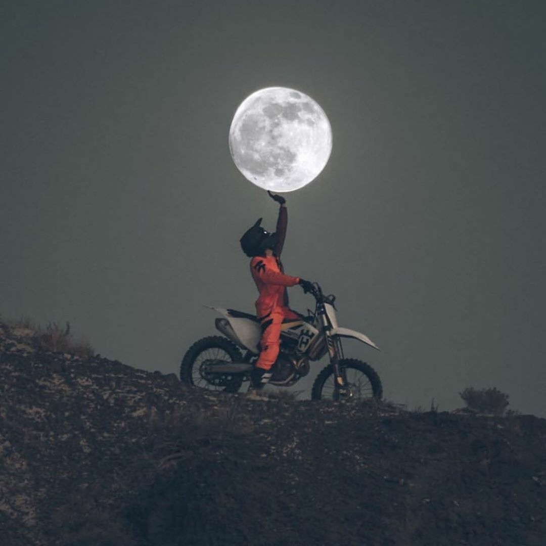 motorcycle rider holding up moon