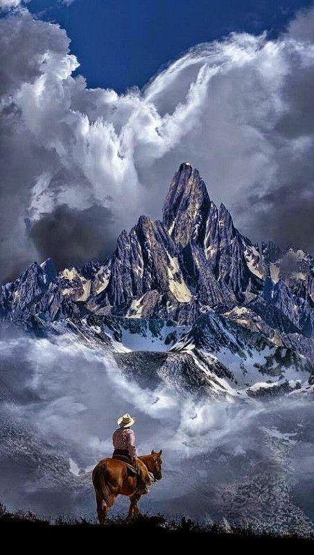 cowboy on horse admiring mountains