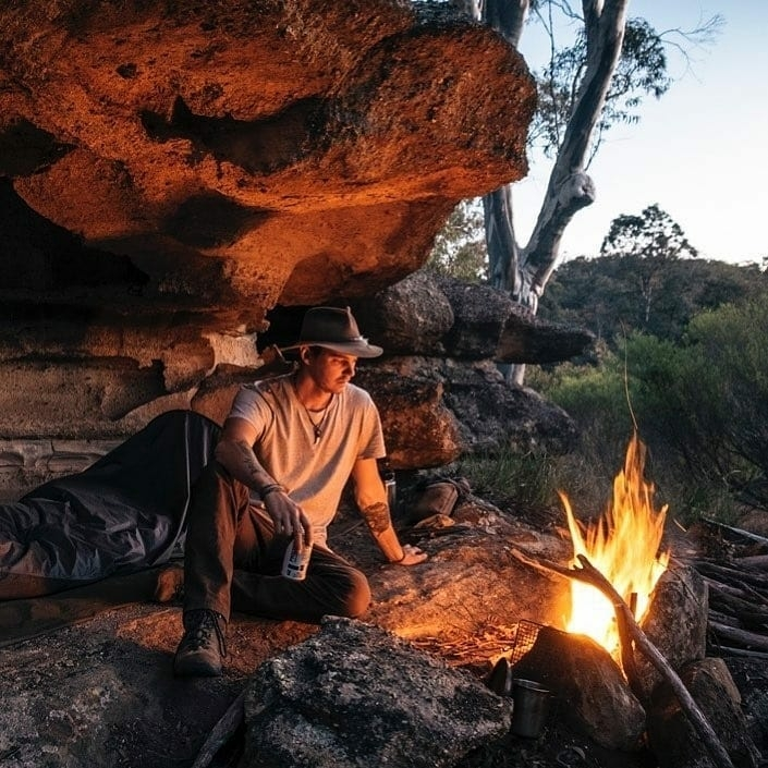 man relaxing by campfire