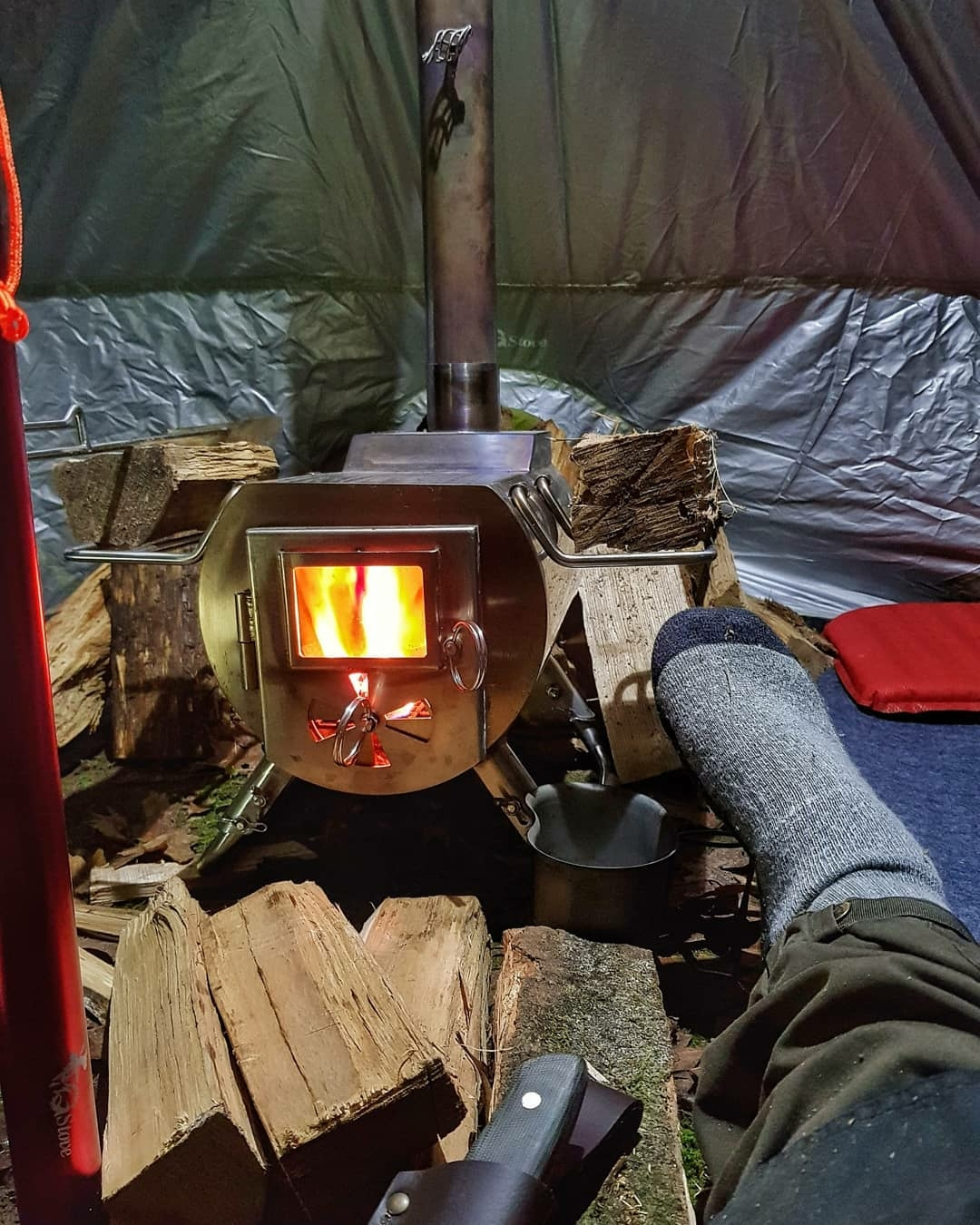 man in tent with stove