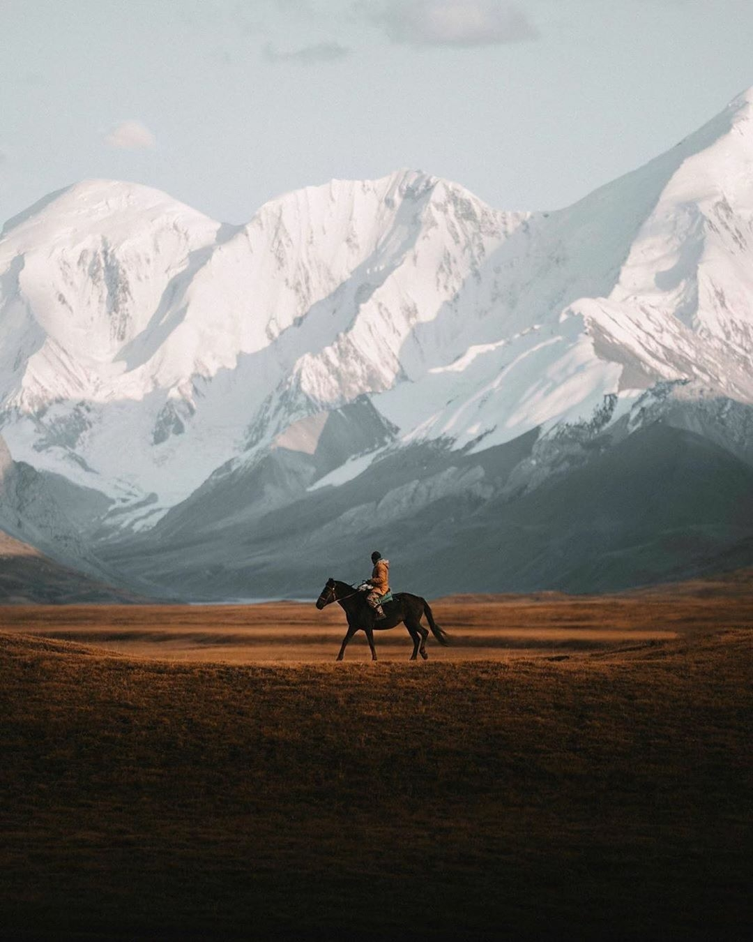 man riding horse with mountains in background