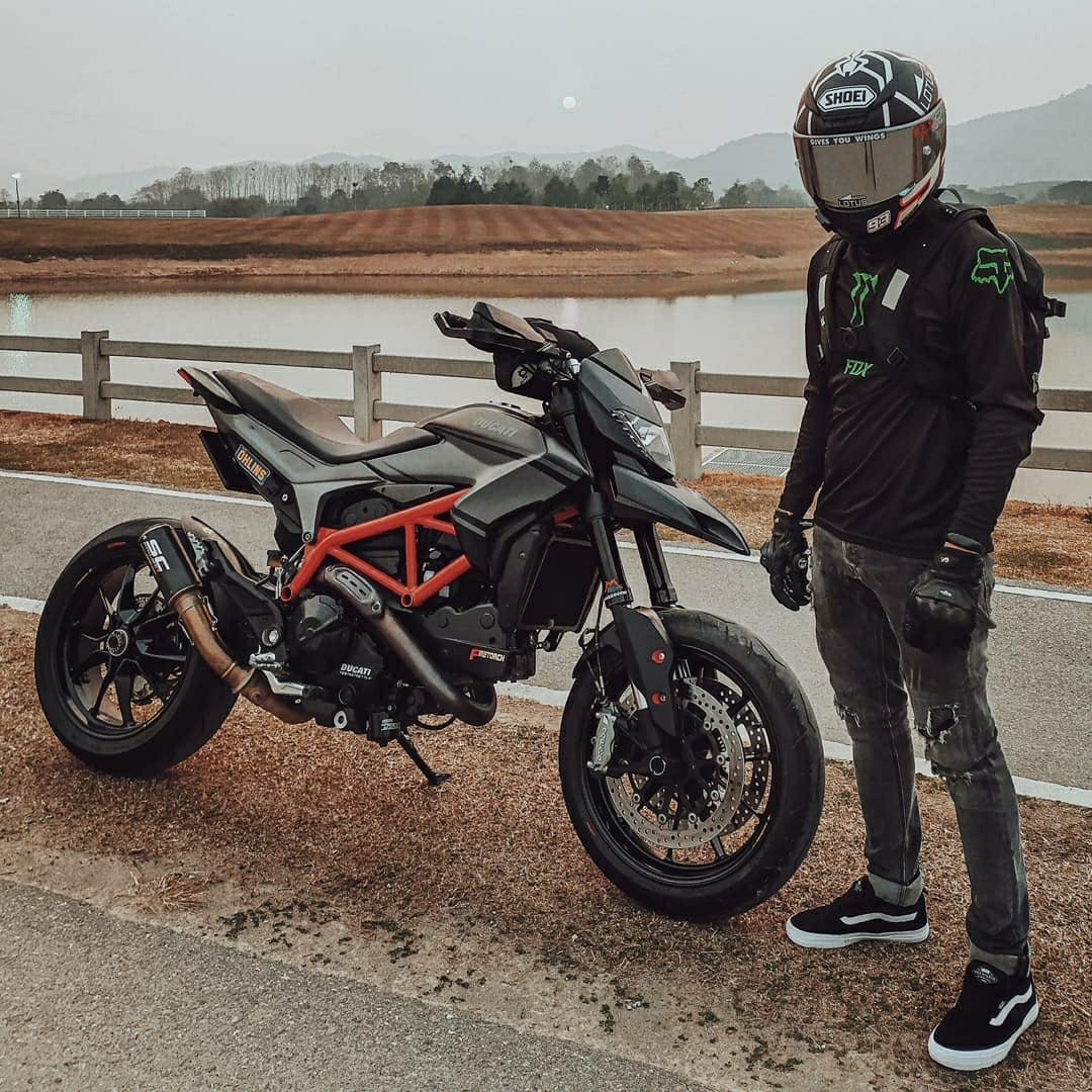 man standing next to ducati on side of road