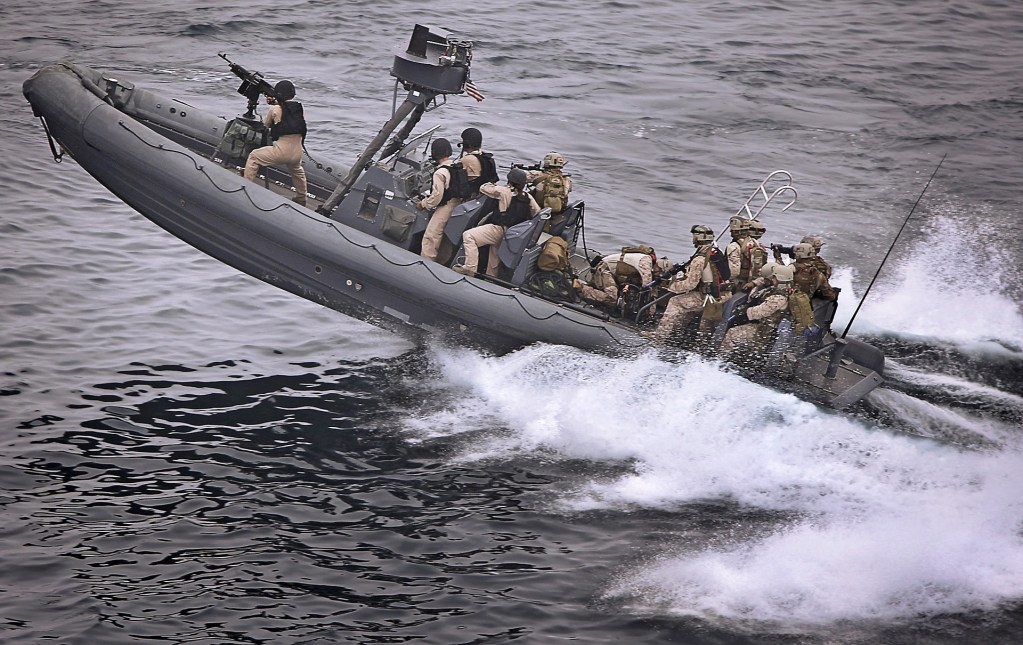 Navy SEALs riding in a gunboat