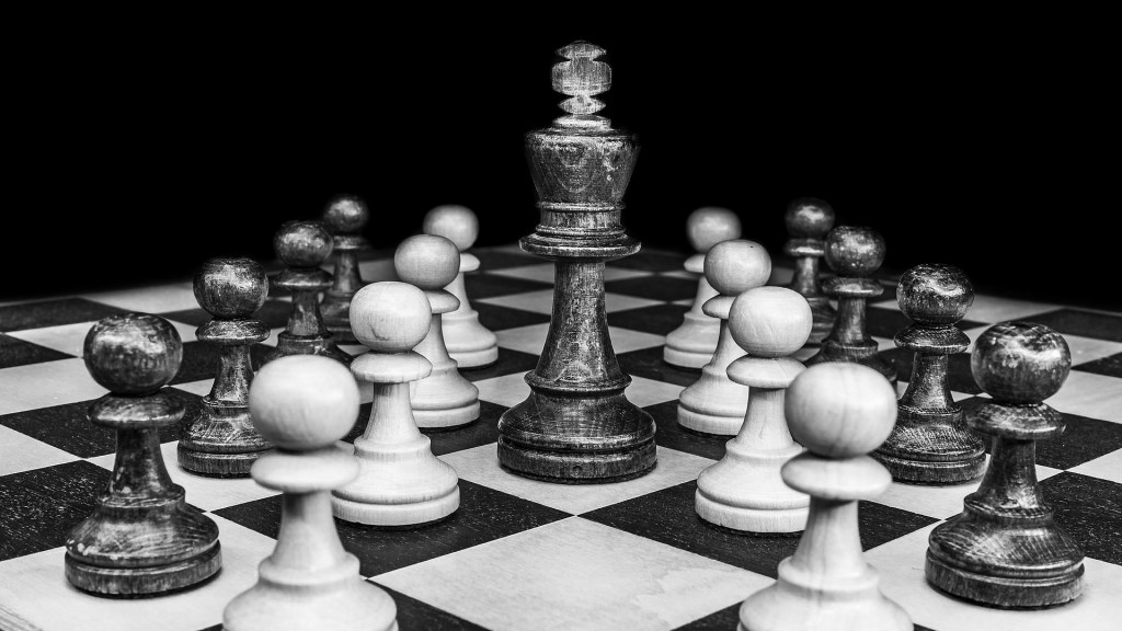 black and white chess board with King standing over other pieces.