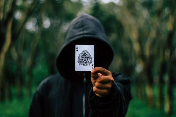 hooded man holding Ace of Spades over his face