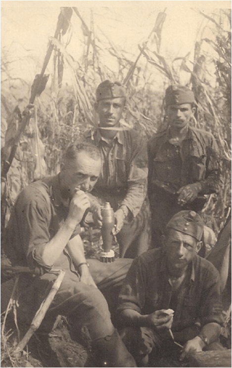 Dad is shown with some of the soldiers in his platoon. Dad is sitting on the left, eating something. The soldier in the rear left is resting a mortar round on Dad's leg.