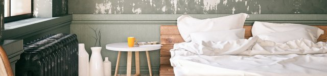Wooden bed with white linen and white table next to the bed with a yellow cup on the table