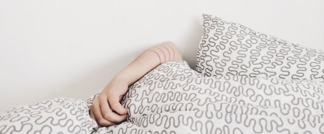 Person sleeping in bed portraying the stages of sleep.