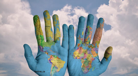 hands with an atlas of the world printed on them