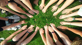 A circle of hands and feet from above