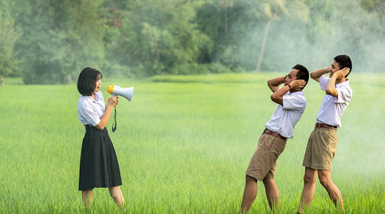 a woman in a field speaking into a megaphone while two men cover their ears