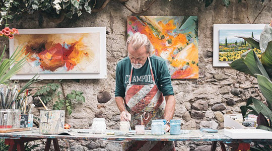 a man in a painting studio with a rustic wall behind him