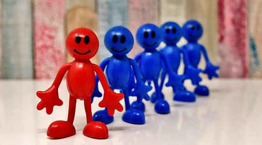 A line of model blue men with one red man at the front