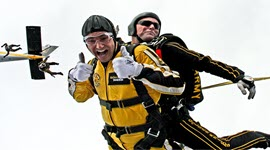 A tandem skydive with the plane in the background