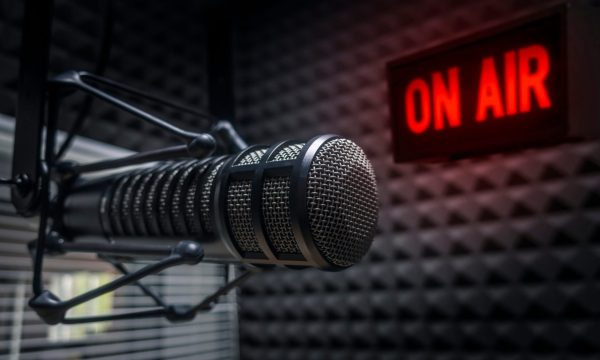 A picture of a microphone in a recording studio, in the back a lit up sign reads, on air.