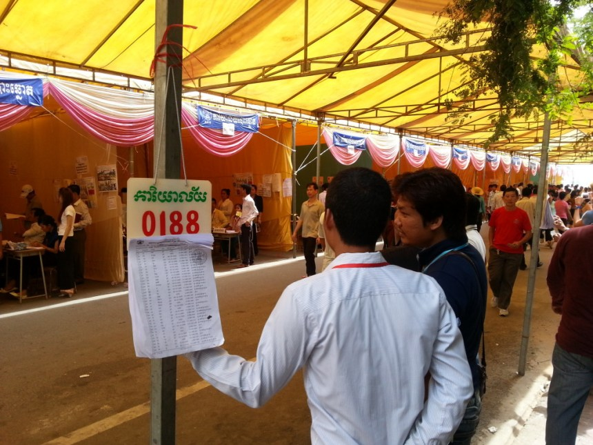 Election monitors keep an eye on the voting Sunday morning on Street 130 near Phnom Penh's riverside.