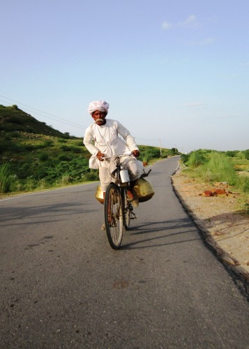 Pushkar milkman rises to the challenge of a small hill on the road in Rajasthan.
