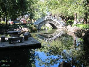 A couple crossing a bridge in a Dali park are reflected in the pond's waters.
