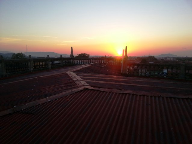 The sun sets in the background, casting a warm glow over the rusty rooftop where we surveyed the city with Miguel
